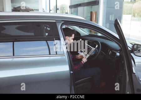Vendeur à l'intérieur de la voiture brochure lecture Banque D'Images