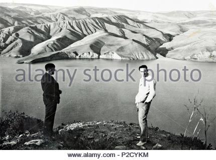 Deux hommes debout sur le dessus d'une crête surplombant un lac et paysage de désert montagneux Maroc 1930 Banque D'Images