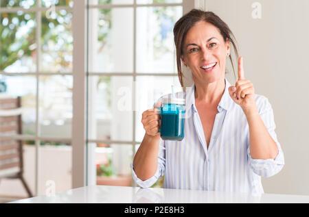 Femme d'âge moyen de lait à boire dans un verre surpris avec une idée ou une question doigt avec happy face, numéro un Banque D'Images