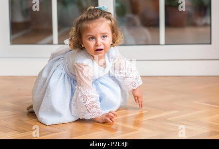 Belle blonde dans une robe enfant pleurer avec un trantrum assis sur le plancher à la maison Banque D'Images
