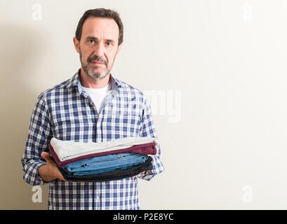 Senior man holding folded blanchisserie vêtements avec une expression confiante face à la pensée intelligente grave Banque D'Images
