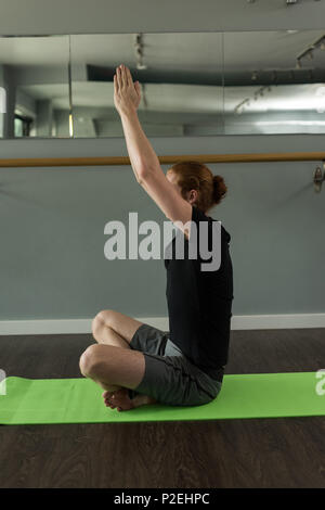 Man practicing yoga on exercise mat Banque D'Images