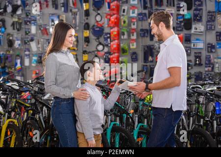Manager with digital tablet aidant à choisir des vélos pour les clients en magasin de vélo Banque D'Images