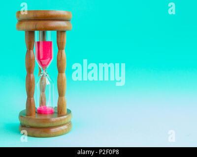 Hourglass Vintage en bois avec sable rose sur fond bleu, sable fonctionnant par les ampoules pour mesurer le temps qui passe dans un compte à rebours jusqu'à échéance. Banque D'Images