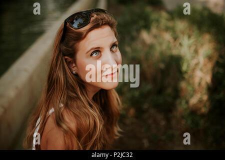 Femme blonde avec des lunettes de soleil dans les cheveux de poser dans le parc Banque D'Images