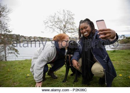 Les femmes amis avec chien-guide en tenant à lakeside selfies Banque D'Images