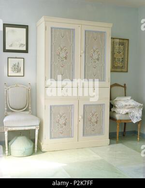 Chaises anciennes de chaque côté de l'armoire peinte avec panneaux à motifs floraux peints à la main dans la chambre de pays Banque D'Images