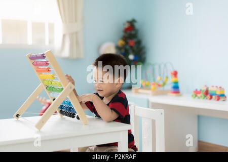 Bébé garçon enfant asiatique apprend à compter. Mignon enfant jouant avec abacus jouet. Petit garçon s'amusant à l'intérieur à la maison. Concept éducatif pour tout-petit bab Banque D'Images
