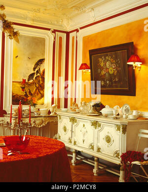 Wall-phares sur chaque côté de peinture au-dessus de buffet peint vintage à Paris élégante salle à manger avec fresque sur mur Banque D'Images