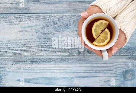 Close up of female hands holding cup of sex tee sur bureau en bois avec copie espace Banque D'Images