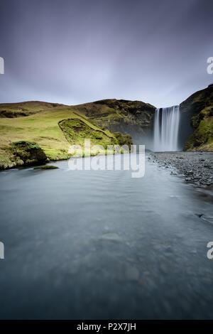 Belle Skogafoss. Un paysage extraordinaire au coucher du soleil dans la cascade les plus populaires en Islande. Effet d'une exposition longue. À l'aube dans la rocade. Banque D'Images