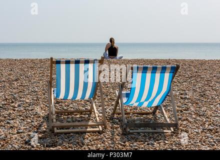 Deux chaises longues sur la plage de Brighton avec une jeune femme assise au soleil. Banque D'Images