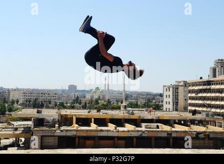 Alep, Syrie. 8 juin, 2018. Un jeune Syrien parkour player exécute un backflip du haut d'un bord dans la partie endommagée de-en grande partie la ville d'Alep, Syrie du nord, le 8 juin 2018. Avec leur vue imprenable flips et cascades de saut, un groupe de jeunes Syriens sont donnant vie à la détruit certaines parties de la ville d'Alep avec leur performance électrisante Parkour. Pour aller avec: Les jeunes Syriens raviver la vie dans les ruines du vieux Alep avec l'électrification de Parkour performance. Credit: Ammar Safarjalani/Xinhua/Alamy Live News Banque D'Images