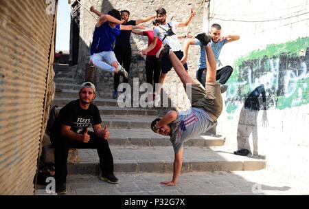 Alep, Syrie. 8 juin, 2018. Les jeunes joueurs effectuer un Syrien parkour saut coordonné dans la partie endommagée de-en grande partie la ville d'Alep, Syrie du nord, le 8 juin 2018. Avec leur vue imprenable flips et cascades de saut, un groupe de jeunes Syriens sont donnant vie à la détruit certaines parties de la ville d'Alep avec leur performance électrisante Parkour. Pour aller avec: Les jeunes Syriens raviver la vie dans les ruines du vieux Alep avec l'électrification de Parkour performance. Credit: Ammar Safarjalani/Xinhua/Alamy Live News Banque D'Images