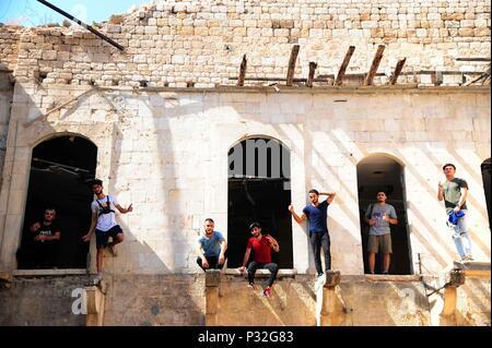 Alep, Syrie. 8 juin, 2018. Les jeunes joueurs parkour syrienne se tenir sur le bord d'une maison endommagée en grande partie dans la partie endommagée de la ville d'Alep, Syrie du nord, le 8 juin 2018. Avec leur vue imprenable flips et cascades de saut, un groupe de jeunes Syriens sont donnant vie à la détruit certaines parties de la ville d'Alep avec leur performance électrisante Parkour. Pour aller avec: Les jeunes Syriens raviver la vie dans les ruines du vieux Alep avec l'électrification de Parkour performance. Credit: Ammar Safarjalani/Xinhua/Alamy Live News Banque D'Images