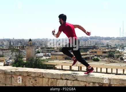 Alep, Syrie. 8 juin, 2018. Un jeune Syrien parkour player s'étend le long du bord d'un haut mur en grande partie dans la partie endommagée de la ville d'Alep, Syrie du nord, le 8 juin 2018. Avec leur vue imprenable flips et cascades de saut, un groupe de jeunes Syriens sont donnant vie à la détruit certaines parties de la ville d'Alep avec leur performance électrisante Parkour. Pour aller avec: Les jeunes Syriens raviver la vie dans les ruines du vieux Alep avec l'électrification de Parkour performance. Credit: Ammar Safarjalani/Xinhua/Alamy Live News Banque D'Images