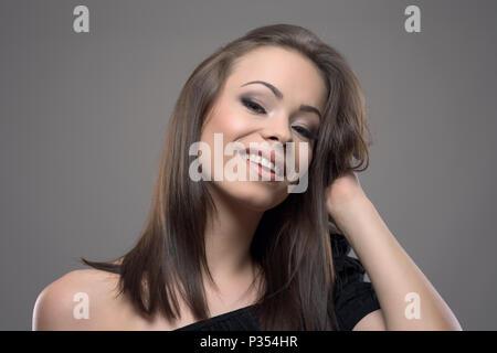 Belle jeune femme glamour de toucher les cheveux bruns en bonne santé et souriant à la caméra en contre fond gris. Banque D'Images