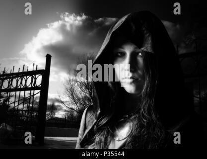 Portrait d'une jeune fille dans une robe avec une capuche près du cimetière sur le coucher du soleil noir et blanc Banque D'Images