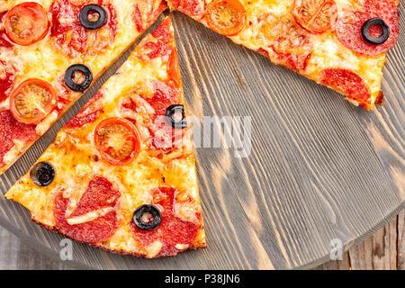 Pizza au pepperoni, sur planche de bois Banque D'Images