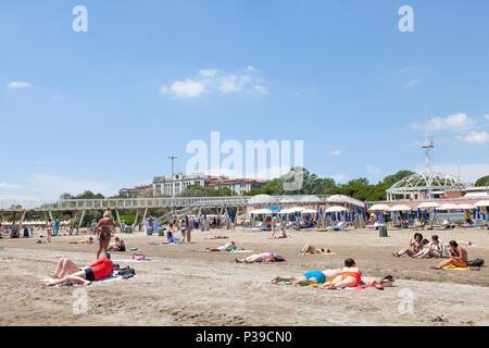 Les gens en train de bronzer sur le sable en face de la jetée et restaurant, Blue Moon Beach, Lido di Venezia, l'île du Lido, Venise, Italie à la fin du printemps Banque D'Images
