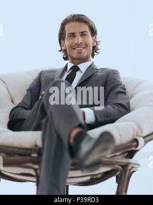 Handsome businessman assis dans un grand fauteuil confortable. Banque D'Images