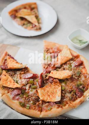 Pizza italien frais. La photographie alimentaire pour la conception. Pizza mexicaine avec les morceaux, l'oignon, piment jalapeno chaud sur une fine couche de pâte classique. Photo gros plan de coupe. Banque D'Images