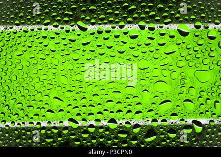 Gros plan d'une goutte d'eau sur un fond rayé noir et vert, couvert de gouttes d'eau -la condensation. Banque D'Images