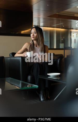 Asian businesswoman looking loin tout en maintenant tasse à café et téléphone mobile Banque D'Images