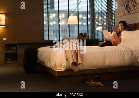 Businesswoman sitting on bed holding documents tout en utilisant son téléphone portable Banque D'Images