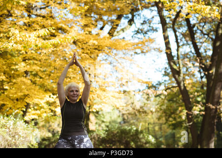Senior woman practicing yoga in a park Banque D'Images