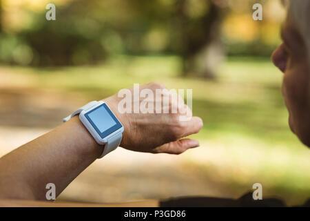 Senior woman à l'aide d'un smart watch dans un parc sur une journée ensoleillée Banque D'Images