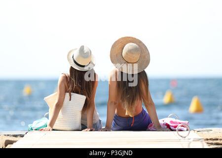 Vue arrière de deux touristes à l'horizon au-dessus de la mer en vacances de détente sur la plage Banque D'Images