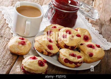 Petits pains anglais avec appliques de groseille rouge sont servis avec de la confiture et du thé anglais close-up sur la table horizontale. Banque D'Images