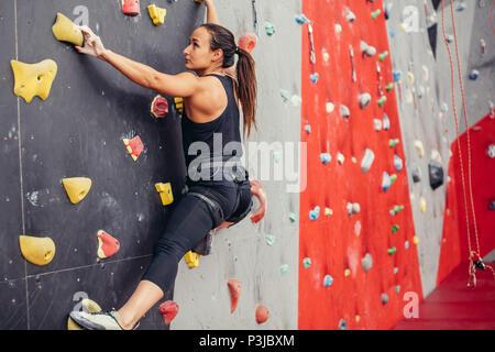 Jeune femme grimpeur d'escalade sur roche pratique en centre d'escalade, le bloc Banque D'Images