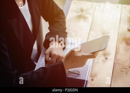 Close up business woman using smartphone tout en étant assis à la cafétéria. Concept de business mobile. Libre avec une séle Banque D'Images