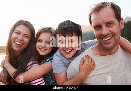 Portrait de parents Donner aux enfants Piggyback Ride In Countryside Banque D'Images