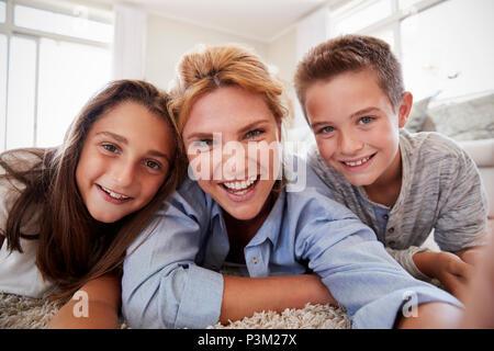 La mère et l'enfant couché sur un tapis et se faisant passer pour à la maison Selfies Banque D'Images