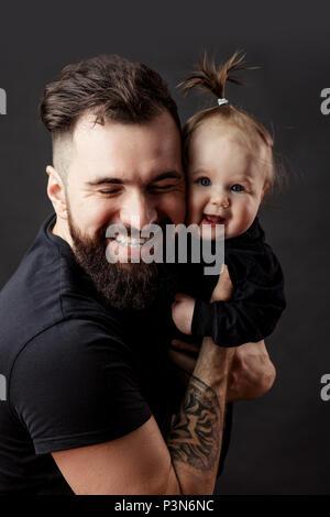 Beau jeune homme tatoué holding cute little baby sur fond noir Banque D'Images