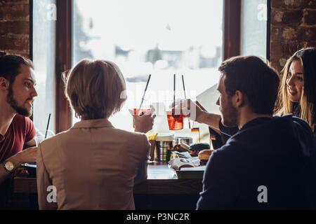 Vue arrière de Compagnie des jeunes gens heureux de parler alors qu'il était assis au café Banque D'Images