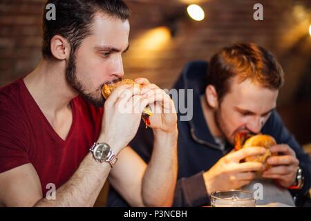 Deux amis heureux de manger des hamburgers savoureux en bar. Banque D'Images
