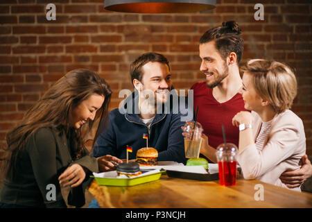 Groupe de jeunes rencontre d'amis dans le café. Banque D'Images