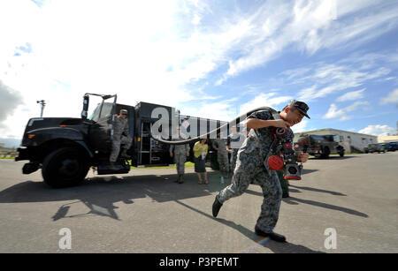 Japan Air Self Defense Force Le Capitaine Takehiro Okabayashi HQs, le sud-ouest de la Division de l'air composites, Base aérienne de Naha, tirant le démontre d'un tuyau de carburant R-11 camion pendant leur tournée, le 21 juillet 2016, à Kadena Air Base, au Japon. Les avantages de cette tournée pour les deux parties sont l'occasion de réseautage professionnel tout au long de l'Okinawa fossiles communauté et le partage des idées sur les méthodes les plus efficaces pour la livraison de l'équipement et le carburant aviation. (U.S. Air Force photo par Naoto Anazawa) Banque D'Images
