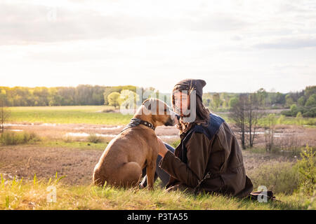 Belle randonnée girl s'asseoir sur la colline avec le chien à marcher. Jeune femme avec chien chinois à meadow lors des chaudes après-midi ensoleillé Banque D'Images