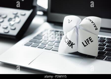 L'origami fortune teller on laptop in office concept pour l'équilibre de vie sains Banque D'Images