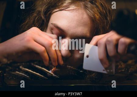 Gros plan des mains d'un jeune homme toxicomane reniflant substance en poudre Banque D'Images