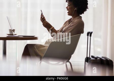 Businesswoman waiting at salon de l'aéroport pour le vol et de faire un appel vidéo à partir de son téléphone mobile. Smiling african female executive en attente à l'aéroport de ar Banque D'Images