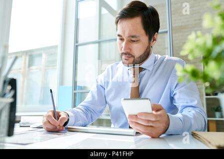 L'employé qui travaille avec le smartphone in office Banque D'Images