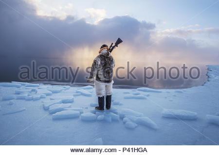 Un chasseur inuit sur l'Arctique rétrécit la glace de mer. Banque D'Images