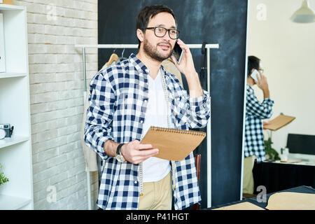 L'homme dans l'atelier de parler sur le téléphone du client Banque D'Images