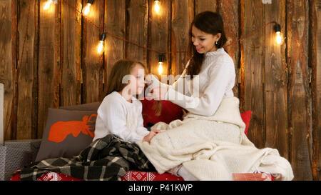 Jeune mère en pull blanc matières à tresser les cheveux de sa fille Banque D'Images